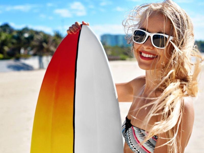 Mulher com óculos de sol na praia  Descrição gerada automaticamente